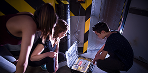People solving puzzles in Hangar 403 at The Locked Room